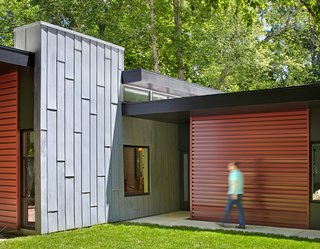 This Light-Filled, Metallic Home Embraces Its Wooded Site - Photo 4 of 8 - A tall gray wall, made of acid-washed zinc metal, marks the entryway and visually grounds the roof planes. It also separates the living and bedroom volumes.