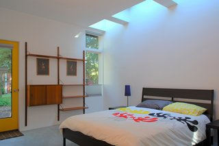 """This Light-Filled, Metallic Home Embraces Its Wooded Site - Photo 8 of 8 - In the bedroom, an IKEA bed frame and CADO wall unit are drenched with natural light during the day from the skylights overhead. """"The effect of daylight through skylights is very different than from a window,"""" Hart says. """"You feel every minute of the day as light in the space ebbs and flows with the passing clouds."""""""