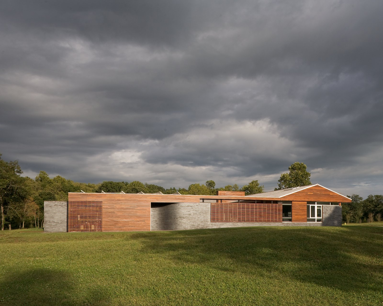 The project was dubbed the Curved House because one of the main requests from the client was the integration of curved lines throughout the project. Outside, the most notable example of this is the exterior brick wall that emerges from the sharply linear ironwood walls in soft waves. The roof is also made of a curved Spanish tile punctuated by an extensive, angular solar array.