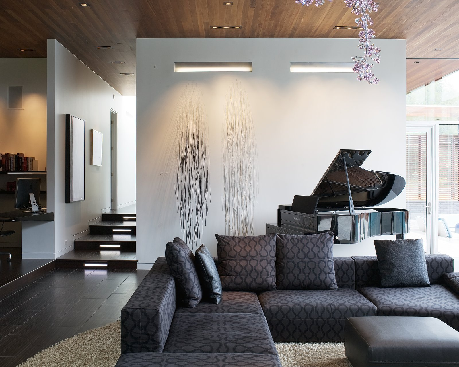 In the living room, several art installations add flair, including one special addition from Anne Lindberg, an artist known for understated line drawings. Strands of welding wire with tiny sculpted wood ends were drilled into the wall near the piano so they would stick out and move with breezes from the courtyard. Its cascading lines contrast directly with the curvilinear, soft pink Swarovski crystal chandelier by Tord Boontje.