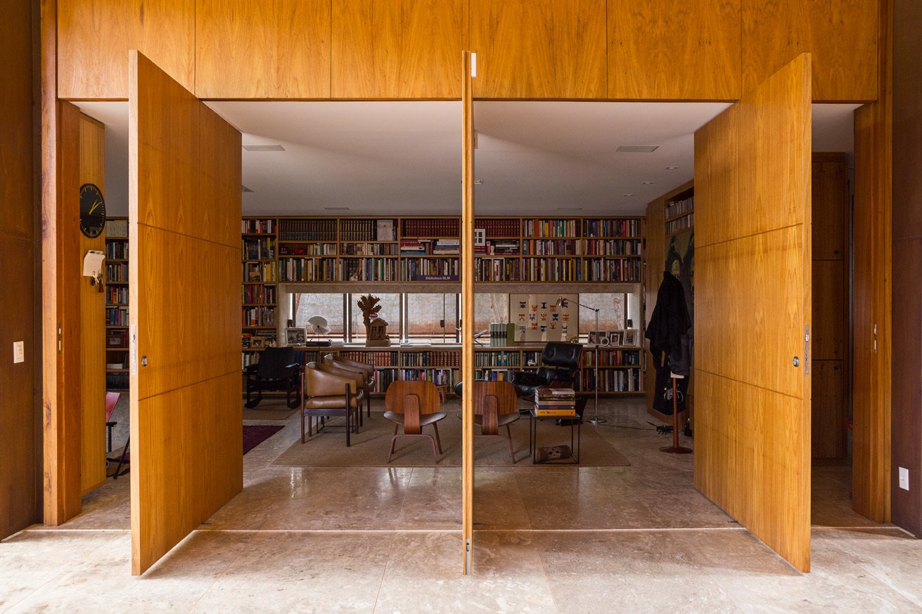 The library's entrance features massive panel doors made of tropical freijó wood. Inside, leather armchairs by Jorge Zalszupin accent the space. Tagged: Living Room and Chair.  Photo 8 of 20 in Take a Step Through 20 Huge Modern Doors from House of the Week: Indoor-Outdoor Brazilian Modern Home