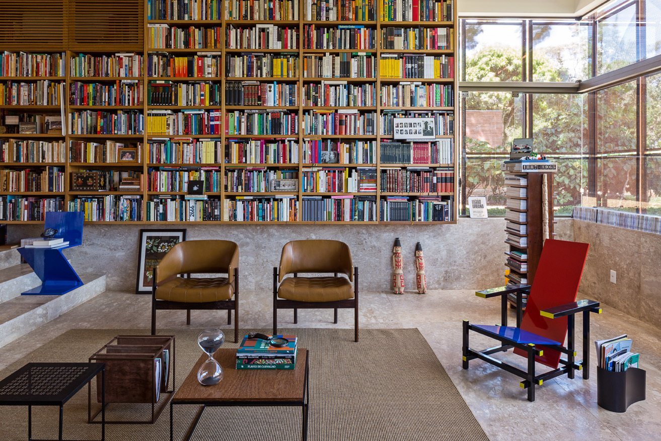 "Architect Gustavo Costa calls the home library the ""project's heart."" This central space houses the owner's expansive collection of about 5,000 books, and acts as a meeting place for friends and colleagues. A Gerrit Thomas Rietveld Red and Blue chair completes the space. Tagged: Living Room, Chair, and Bookcase.  Read by DAVE MORIN from House of the Week: Indoor-Outdoor Brazilian Modern Home"