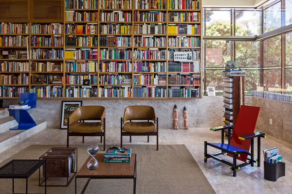 """Architect Gustavo Costa calls the home library the """"project's heart."""" This central space houses the owner's expansive collection of about 5,000 books, and acts as a meeting place for friends and colleagues. A Gerrit Thomas Rietveld Red and Blue chair completes the space."""