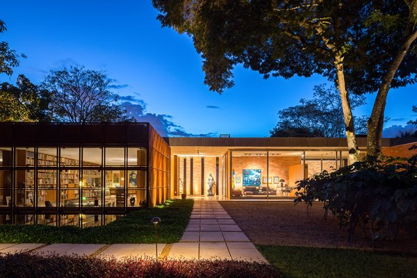 With library's Cor-Ten shield open, the home's facade is seen at night. The L shaped pedestrian pathway forces visitors to travel around the perimeter before entry, gradually experiencing the architectural composition step by step.