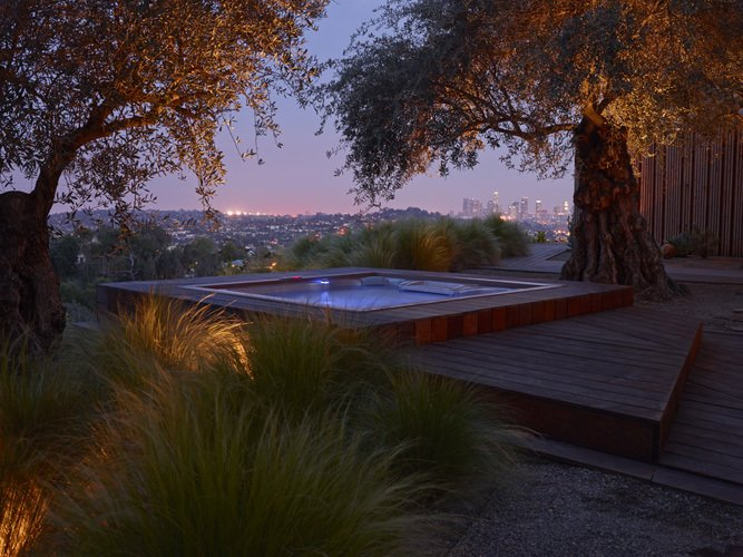 Three olive trees currently anchor the hot tub and deck area. The architects explain that transplanting them with a crane essentially positioned on a cliff face was one of the biggest challenges of the project.  Photo 4 of 11 in 10 Modern Hot Tubs from A Spa-Like Patio with Stunning Views Cascades Down a Los Angeles Hillside