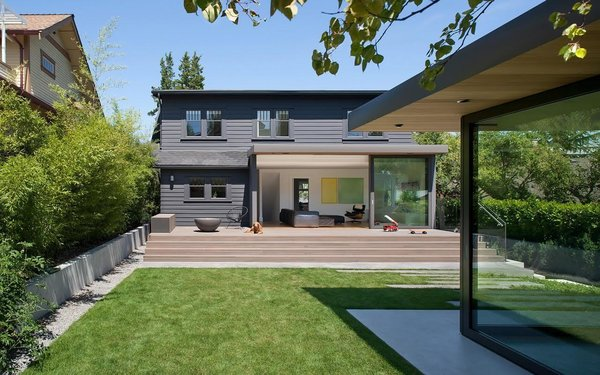 The landscaped backyard acts as a second, open-air living space between the home and garage studio. The cladding on the addition is painted in Benjamin Moore's Iron Mountain, and the deck is stained western red cedar. Photo 15 of Trotman Residence modern home