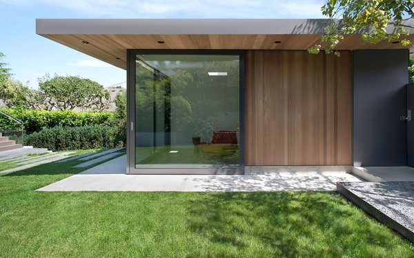 """""""Before, the house turned its back on the landscape,"""" said Parish. """"This renovation and addition really animates the garden."""" Sliding glass doors match those of the living room beyond the deck, and both can be completely open to the yard."""
