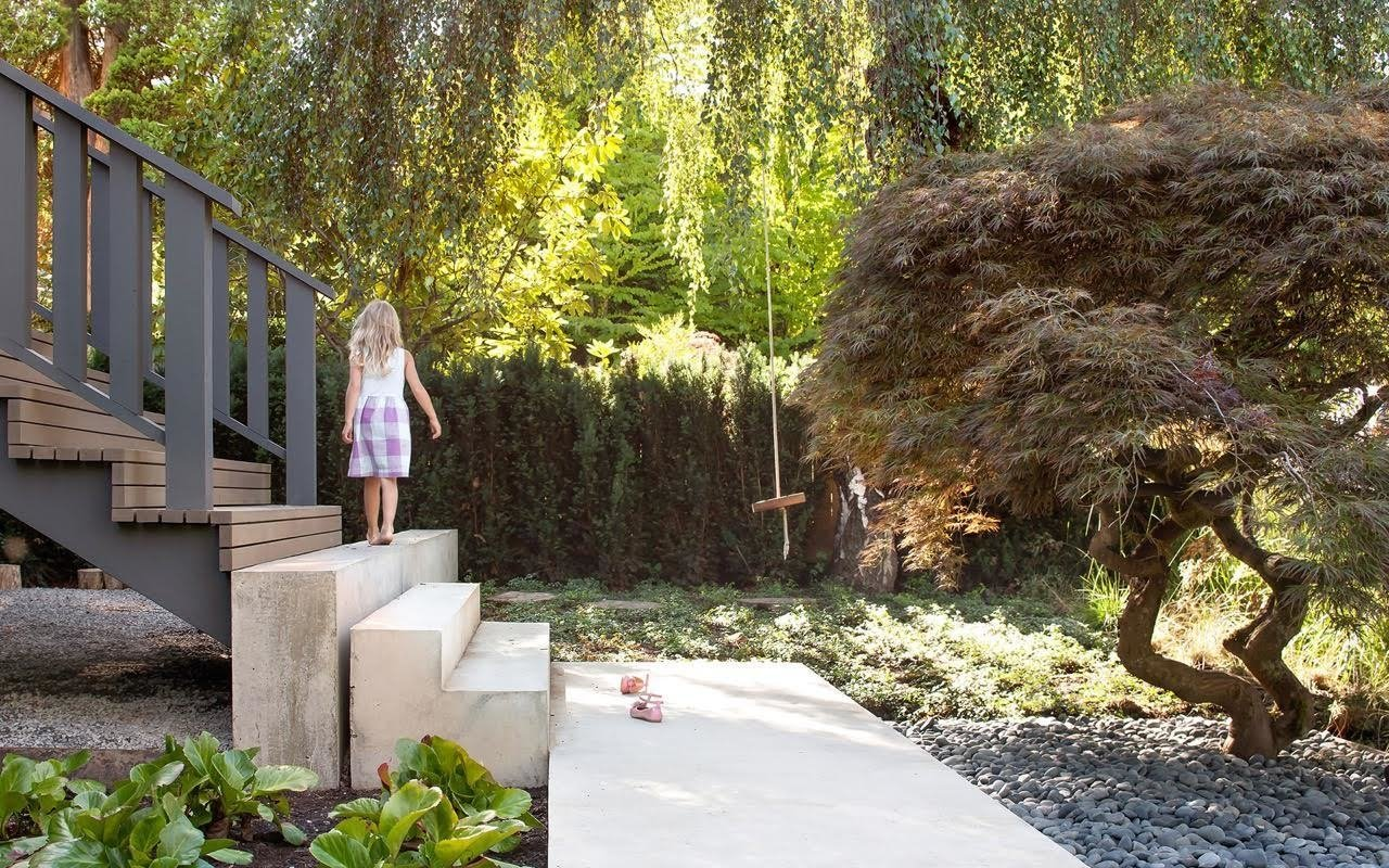 "The backyard's emphasis on nature is mirrored in the front of the home, which also underwent extensive landscaping by Considered Design. The owners and Parish wanted to ""tone everything down"" and turn the home into a backdrop for a natural setting. Tagged: Outdoor, Walkways, Front Yard, and Trees.  Modern Spaces in the Pacific Northwest by William Lamb from A Vancouver Renovation Transforms a Backyard into a Giant Living Room"