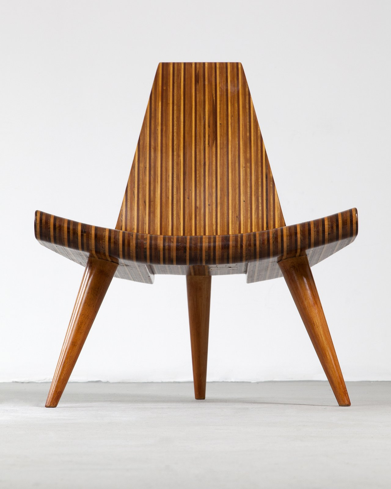 Widely consider the first modern master of Brazilian design, Joaquim Tenreiro created many timeless classics. His contribution to Brazilian design is evident by his designs that made hardwood furniture sleeker and lighter. Tenreiro's 1947 Three-Legged chair was laminated in multiple woods that included native species such as imbuia, roxinho, jacaranda, ivory, and cabreúa. In this example, the chair is made in five different types of hard wood, with bonded laminated. The chair celebrates the material with its inventive form and combinations of wood.  100+ Best Modern Seating Designs by Dwell from Bring the Best of Brazilian Modernism to Your Home with This New Book
