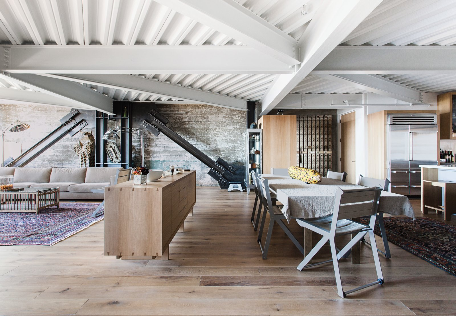 In the new 2,770-square-foot apartment, original I-beams brace the structure at dramatic angles and collide overhead, and the raw concrete is tempered by blackened steel, white-oak flooring, and bush-hammered Carrara marble—all selected by Willis. Tagged: Dining Room, Chair, Table, and Medium Hardwood Floor.  40+ Homes With Exposed Beams: Rustic to Modern by Luke Hopping from Eclectic Homes That Mix Tons of Different Materials