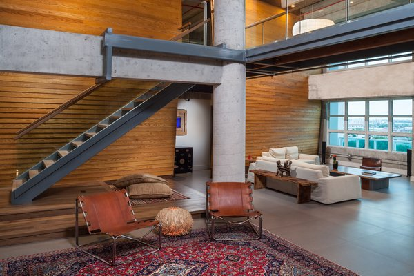 The warped wooden wall backing the living room not only visually counterbalances the coldness of the steel and glass, but also reduces reverbation throughout the entire loft.