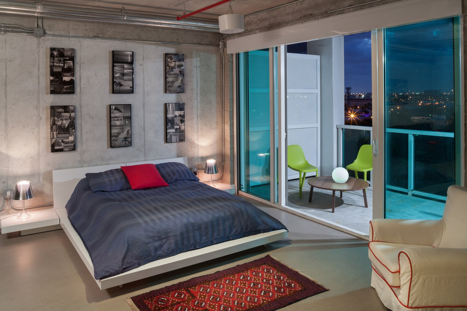 Balcony views and large sliding glass doors add to the tranquil airiness of the master bedoom. Tagged: Bedroom, Night Stands, Bed, and Table Lighting.  Photo 7 of 7 in A Miami Renovation That Blends Concrete and Rich Wooden Interiors