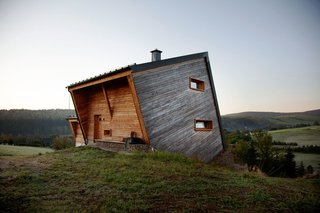101 Best Modern Cabins - Photo 25 of 101 - Sebastian Heise's wooden structure, seemingly atilt, overlooks a green valley in Oberwiesenthal, Germany. The two horizontal windows on the side and the front porch give the home its own unique sense of balance.