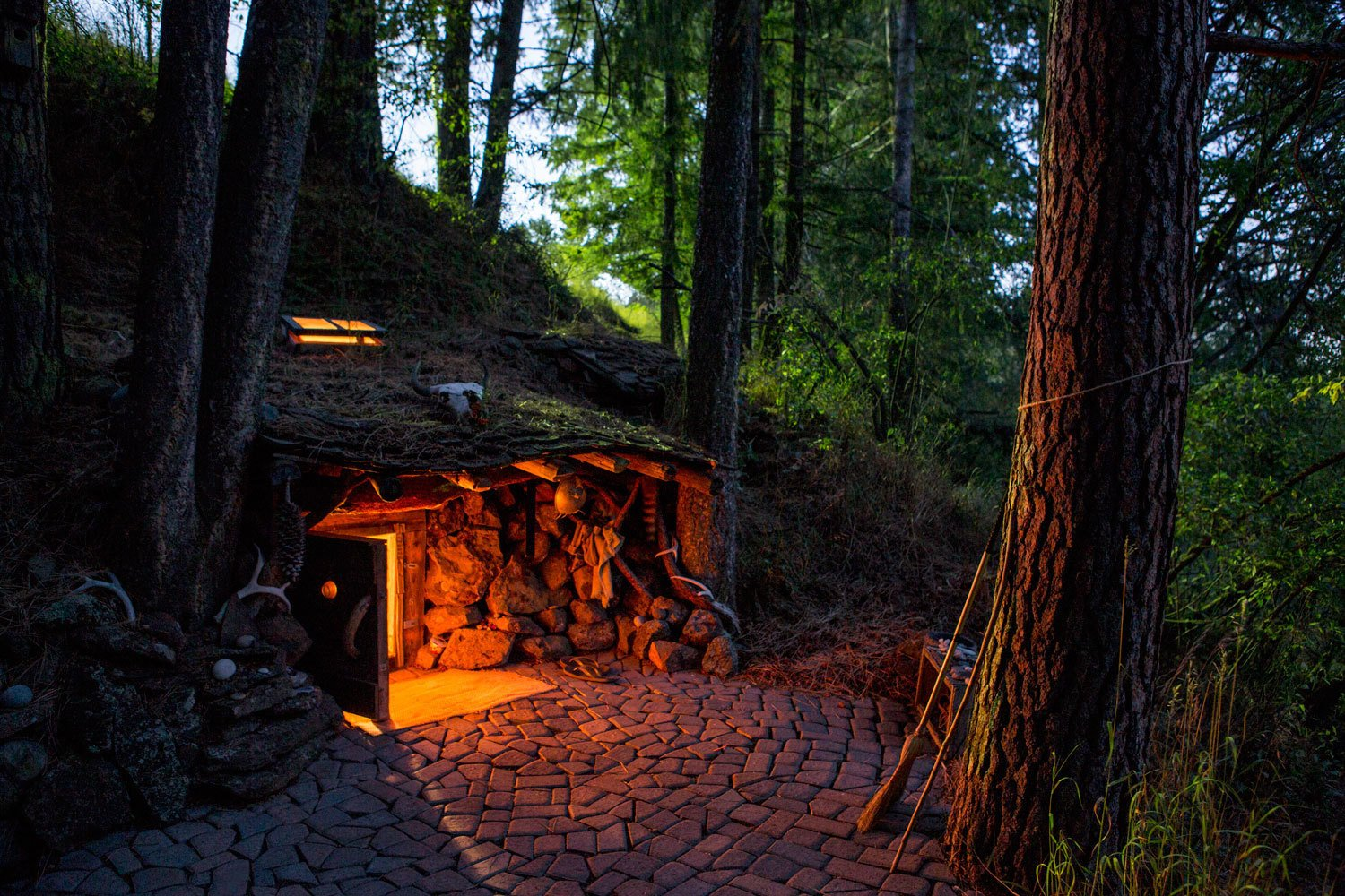 Some cabins are underground, or in the book's taxonomy, Earthen. Dan Price's former home was once broken into and the result was his commitment to live with fewer things, in nature. His hobbit-like home in Joseph, Oregon is complete with tunnels, crawlspaces, and a low-ceilinged bedroom. Using heavy-guage sheeting and wooden structures as roofing elements, he covered the space with dirt to facilitate natural growth above.  Daring Hillside Homes by Diana Budds from Tour 8 Awesome Tiny Cabins Around the World