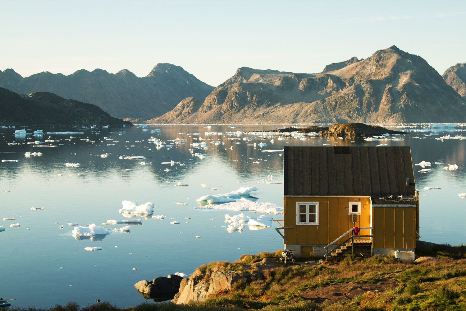 In Kulusuk, East Greenland, Haukur Sirgurdsson enjoys the reflections of a large lake speckled with floating ice chunks.  Off the grid by Michela O'Connor Abrams from Tour 8 Awesome Tiny Cabins Around the World
