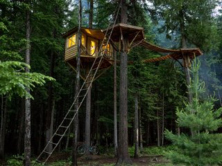 "Photo Essay: Enchanting Tree Houses - Photo 1 of 24 - Ethan Schussler built his first tree house at 12 years old. His today, in Sandpoint, Idaho, sits 30 feet above the ground and is accessed, if not by the rope ladder, an ""elevator"" consisting of a bicycle that, when pedaled, ascends a pulley system to the top."