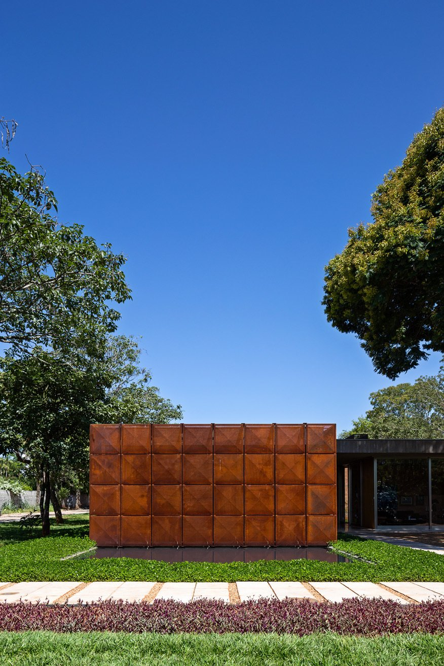 The geometric front facade of the home is made of Cor-Ten steel, segregated into eight vertical panels. Juxtaposed with its lush natural environment, the front elevation is a minimal and abstract counterpoint to its surroundings. An exterior pool meets the facade at its base. Tagged: Exterior, House, and Metal Siding Material.  12 Ways to Get Creative With Cor-Ten Steel by Matthew Keeshin from Homes With Cor-Ten Steel Facades