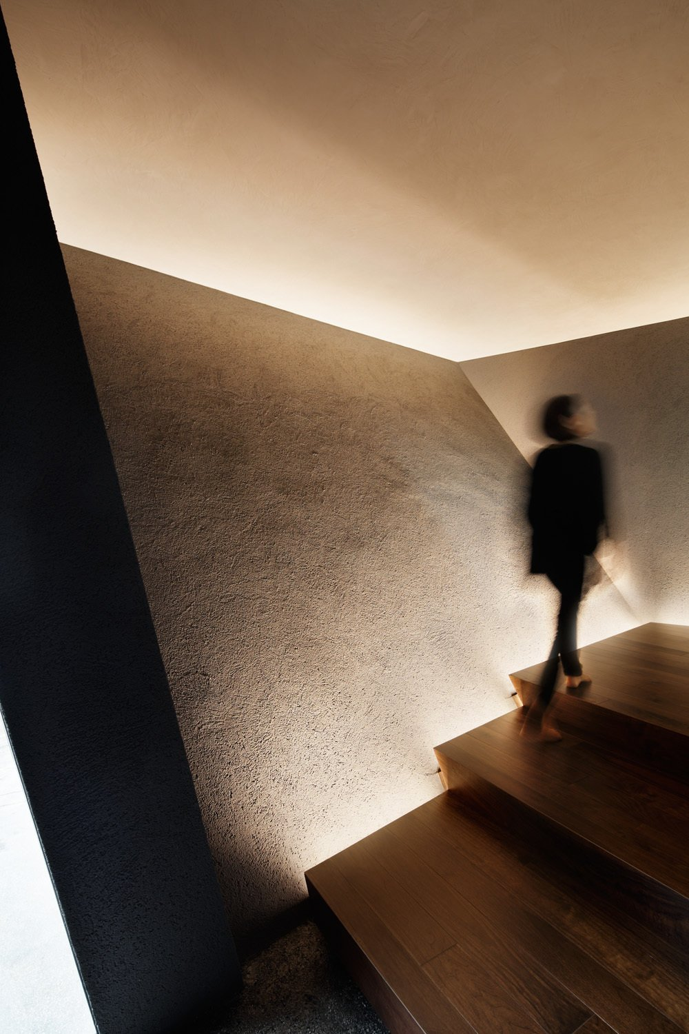 Walnut stairs are side-lit by LEDs.
