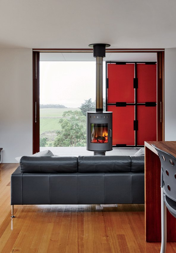 The fireplace, by Rais, can rotate in different directions for both indoor and outdoor use.  Photo 5 of 10 in An Off-the-Grid Prefab that Combines Open Plan Living with Rugged Durability