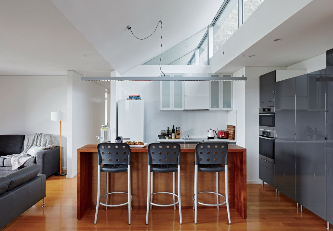 Inside, bar stools by Anibou, appliances by Miele, and gray cabinets from IKEA furnish a simple kitchen.