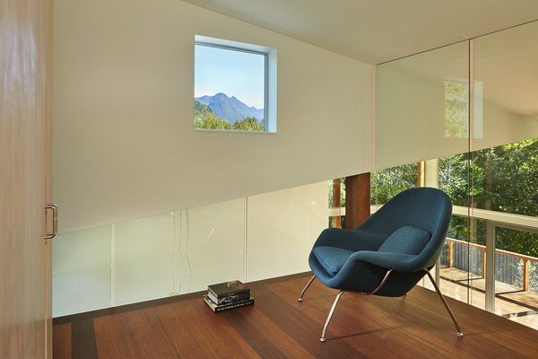 Every room in the home has views to the outdoors, including the loft. Glass walls box in Womb Chairs by Modern Classics.