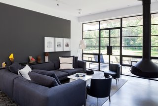 A Couple Takes an Unassuming Plot of Land and Calls it Home - Photo 11 of 11 - Situated near the south-facing facade, the main living space is furnished with a Michel sectional from B&B Italia, Feel Good side chairs by Flexform, and a suspended Ergofocus fireplace from Focus.