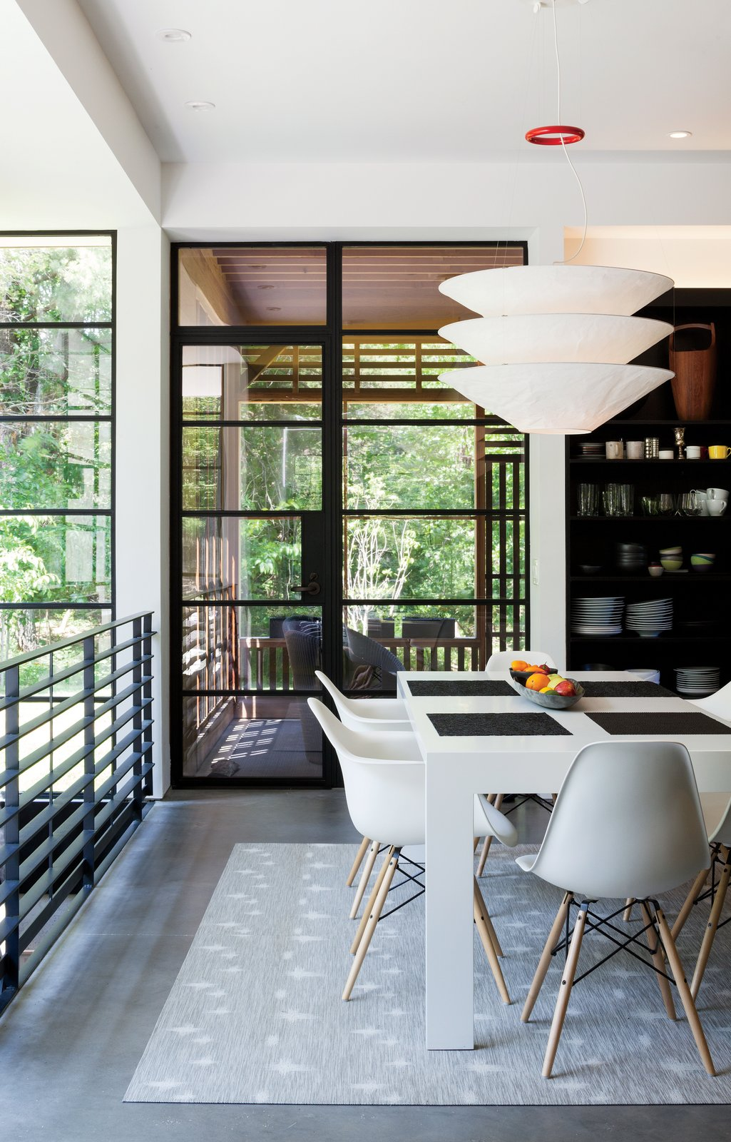 In the dining area are a Gamma table by Cappellini, Eames molded plastic chairs, and a Flotation pendant by Ingo Maurer.