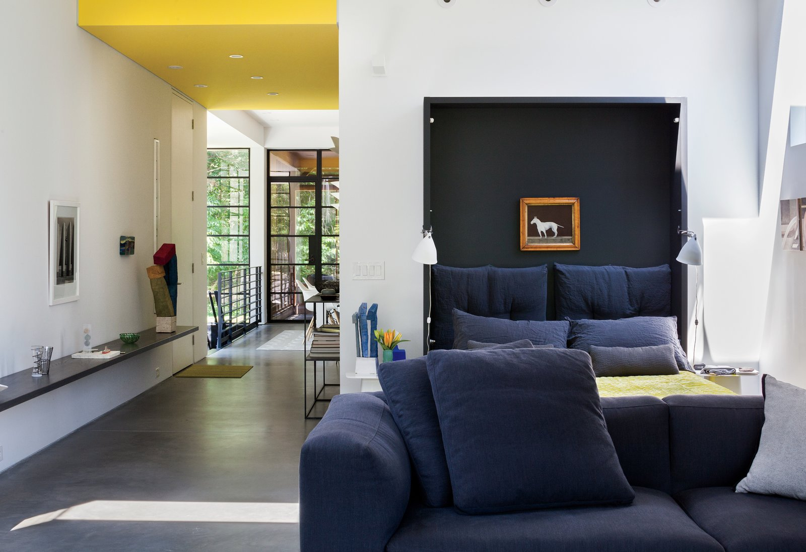 When folded down, deep navy-blue cushions give the effect of a lush headboard. While the home does not yet have a proper master bedroom, the couple plans to create an addition sometime next year.