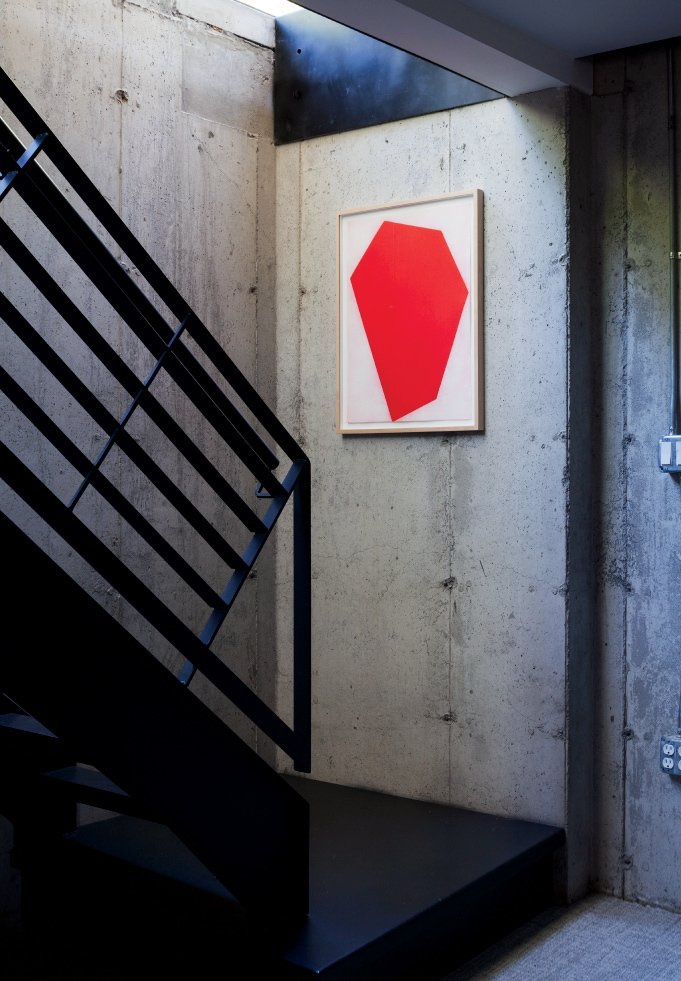 A red print by Cris Gianakos accents a well-lit stairwell leading to a laundry area, library, and rec room on the full basement floor. A Couple Takes an Unassuming Plot of Land and Calls it Home - Photo 7 of 12