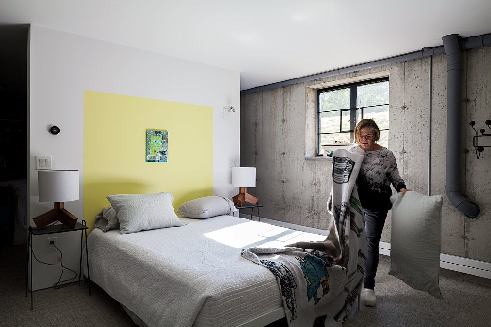 Furnished with Rakks shelving, a Blu Dot table, and a sofa bed from ABC Carpet & Home, the floor also includes a spacious guest bedroom. A bright-yellow color accent, painted onto the wall in Benjamin Moore's Sunburst, acts as a subtle, minimalist headboard.