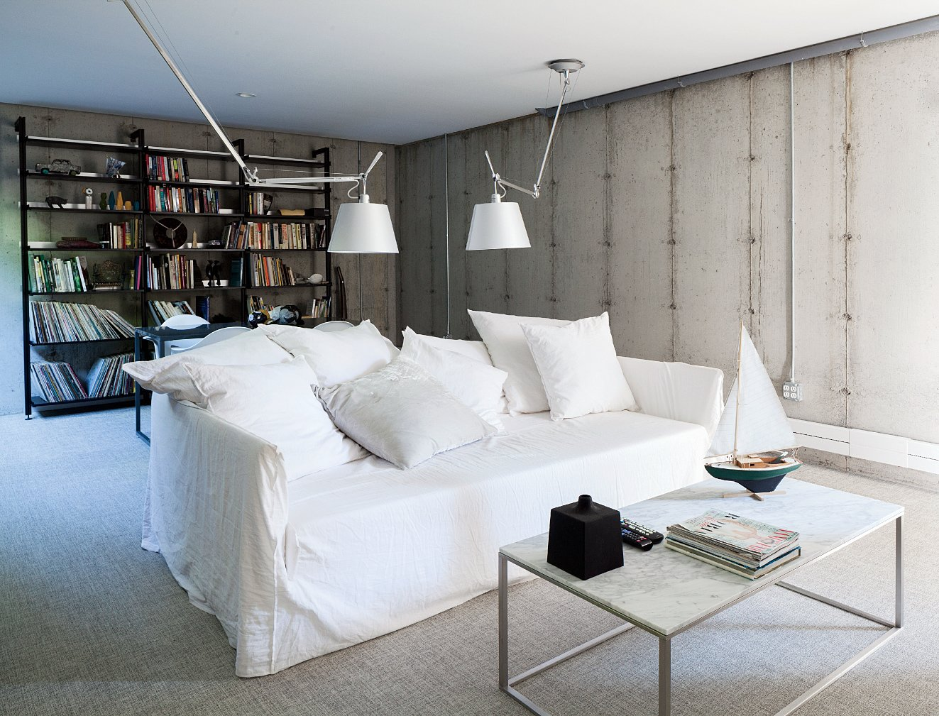 """We sleep in a Murphy bed, but we never close it; it's like living in a loft.""—Sandy Chilewich, resident Tagged: Living Room and Sofa.  concrete by Nir Karpovsky from A Couple Takes an Unassuming Plot of Land and Calls it Home"