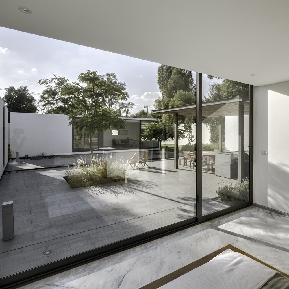 The interior marble flooring and exterior granite surfacing blend well to complement the spare white modules. Both materials were chosen with climate in mind: granite because it both absorbs less heat and is easy to clean, marble because it cools down the interior.  Photo 5 of 7 in A Minimalist Mexican Retreat Uses an Array of Strategies to Beat the Heat from A Minimalist Mexican Retreat that Uses an Array of Strategies to Beat the Heat