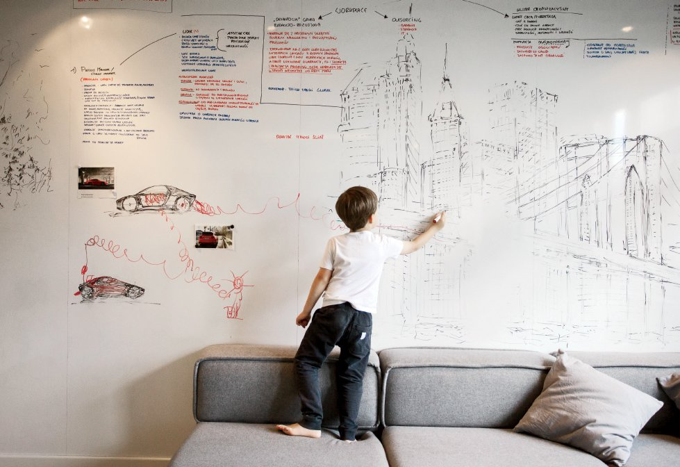 An entire wall is covered with a dry-erase surface from Formica, where Parzyszek and his son Bartek can sketch. Tagged: Living Room and Sofa.  Photo 7 of 11 in 10 Best Dwell Studios and Modern Apartments from This Tiny Warsaw Studio Instantly Changes from Office to Playroom