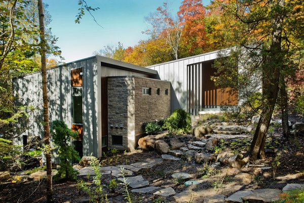 """""""The site was beautiful as it is,"""" architect Eric Tremblay said, and he wanted to build a home that had the least impact on the terrain as possible. The lake can be seen on either side of the house, and natural materials—like the Eramosa limestone coating on the exterior—were a priority during construction. Photo  of Chalet Lac Gate modern home"""