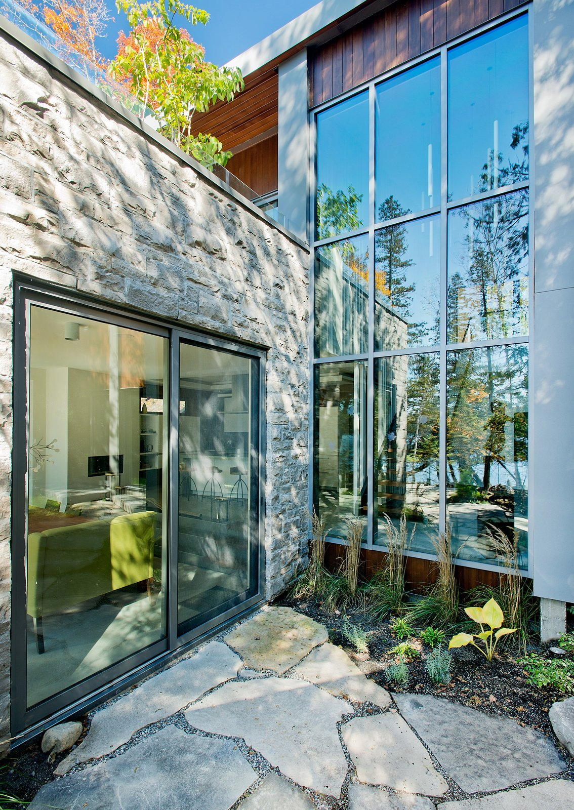 """While the homeowners and their guests have plenty of opportunities to view the outdoors, thanks in large part to windows and doors by Alumilex, an abundance of cedars offers privacy from the outside looking in. """"We wanted to cut the least amount of trees,"""" Tremblay said."""