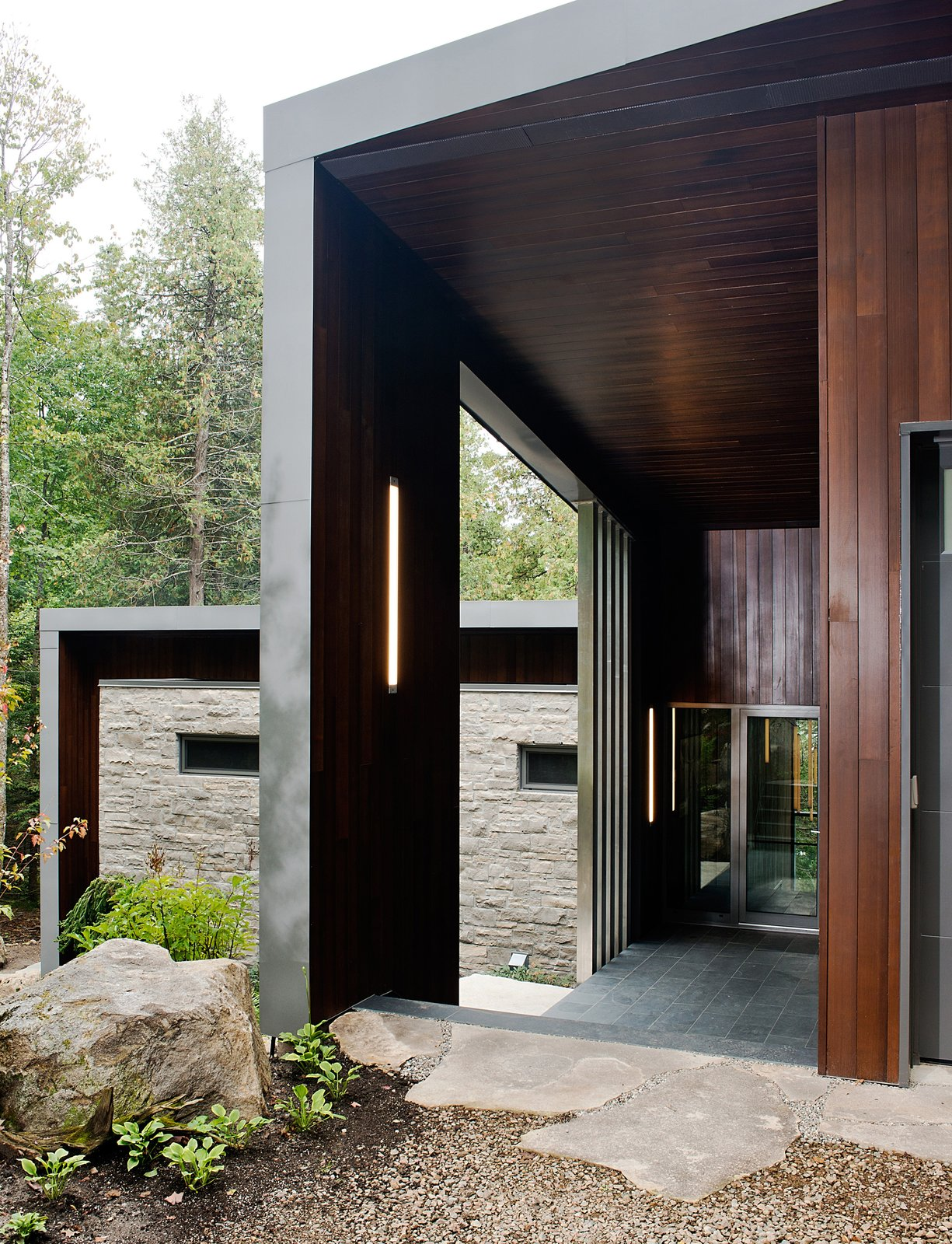 Tremblay chose materials that would reflect the natural setting, like the Polylam-C cedar siding from Prorez, used at the home's entrance. The exterior floor finish is Montauk grey slate.