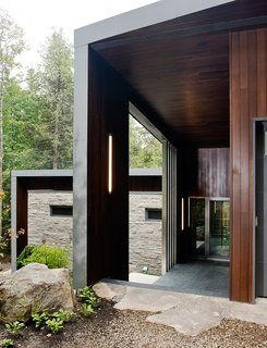 A Tranquil Lakeside Abode in Quebec Unfolds Over Six Levels - Photo 3 of 9 - Tremblay chose materials that would reflect the natural setting, like the Polylam-C cedar siding from Prorez, used at the home's entrance. The exterior floor finish is Montauk grey slate.