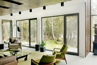 A Tranquil Lakeside Abode in Quebec Unfolds Over Six Levels - Photo 4 of 9 - Low-impact materials were also used for the interior design, which is comprised primarily of concrete, glass, stone, wood, and steel. A palette of mostly light and neutral shades puts the attention on the views.