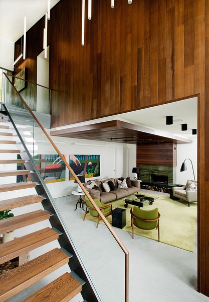 Continuity of exterior and interior materials can be seen in the living room, which is framed by the same Prorez cedar siding as outside. It complements a wood fireplace by Stûv, which is finished with bamboo verde stone and Montauk grey slate.