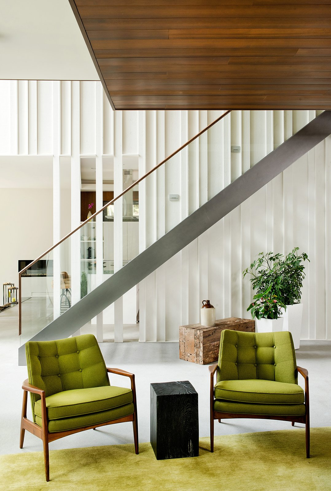 Raw wood planks were painted white and fitted next to a staircase and banister by Bättig Design. Matching chairs by Thayer Coggin sit atop a Crate and Barrel rug.