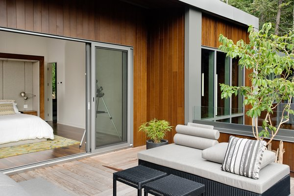 """""""The roof terrace accessed from the master bedroom is the sunniest place, naturally,"""" said Tremblay. A custom-made bed by Boom Town, Tremblay's firm, is outfitted with linens by Kravet. Outdoor seating is by Jardin de Ville. Photo 7 of Chalet Lac Gate modern home"""