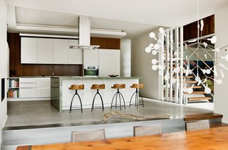 """A Tranquil Lakeside Abode in Quebec Unfolds Over Six Levels - Photo 9 of 9 - """"Riftcut oak panels are used in woodworking and on some kitchen walls,"""" said Tremblay. The design of the cabinets is by Tremblay's firm, Boom Town, with fabrication by Atelier Boisteck. Stools by Arteriors are lined in front of a granite countertop from Costa Esmeralda."""