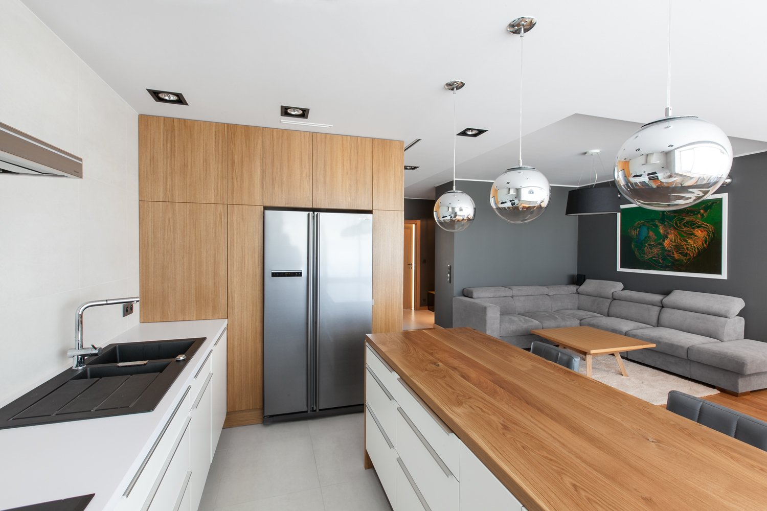 The neutral color palette extends to the kitchen, which is overhung by several pendant globes. Tagged: Kitchen, Wood Counter, and White Cabinet.  Photo 6 of 10 in 10 Open Kitchen Solutions That Will Get Things Cooking from An Open-Plan Apartment Renovation in Poland