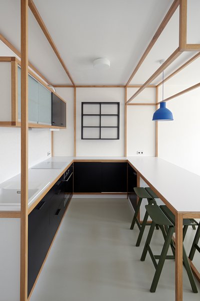A kitchen, complete with a small dining area, allows guests to reverse roles and host the hosts. The blue Muuto Unfold light accents against the otherwise black and white space; the chairs are Hay Copenhague bar stools.