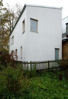 A Compact Home in Moscow Built on the Lowest Possible Budget - Photo 2 of 9 - Placed throughout the home's slatted wood exterior, windows are positioned to allow for the most attractive views and ample natural light. The sloped roof design was chosen for its minimal cost, and for its ability to redirect snow away from a neighboring residence.