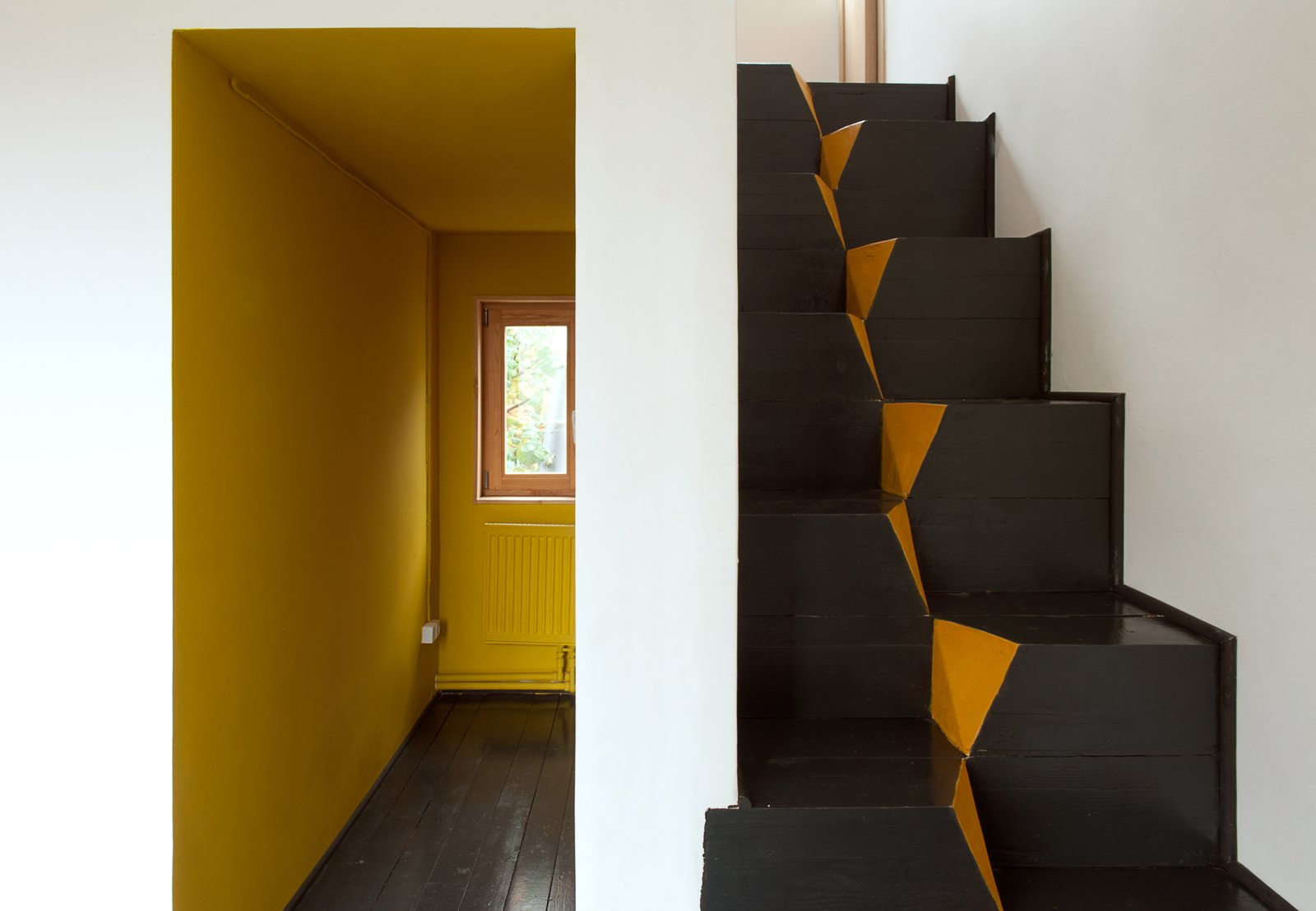 "A corridor-like entrance invites residents into the home. The architects chose to use goose-step stairs because of their safety and efficiency in compact spaces. ""This staircase is also the easiest in terms of construction,"" Kolchin says. ""It is nearly impossible to make any mistake while building it.""  190+ Best Modern Staircase Ideas by Dwell from A Compact Home in Moscow Built on the Lowest Possible Budget"