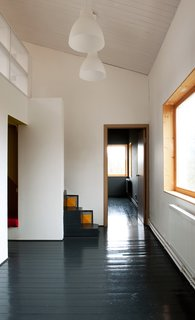 A Compact Home in Moscow Built on the Lowest Possible Budget - Photo 4 of 9 - A pair of lights from IKEA hang above the first floor, which houses the living room, kitchen, and bathroom. Pine floors, painted black, run throughout the residence.
