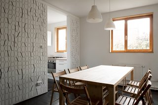 A Compact Home in Moscow Built on the Lowest Possible Budget - Photo 5 of 9 - Chairs and lights from IKEA accompany a custom dining table, which incorporates shelving and storage space underneath.