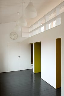"""A Compact Home in Moscow Built on the Lowest Possible Budget - Photo 7 of 9 - Inspired by """"polati,"""" a sleeping loft that featured prominently in traditional Russian homes, Le Atelier created a series of tiny bedrooms that connect to a playroom with a study upstairs. A clock and lights from IKEA blend into the room's simple color palette."""