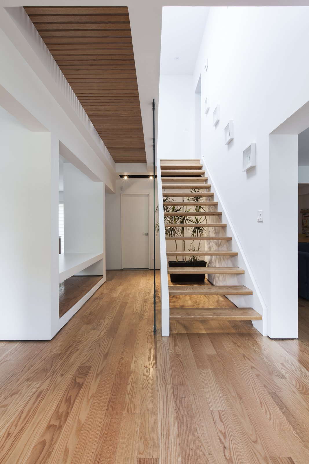 A staircase forms the core of the 1,800-square-foot home, with a symmetrical alcove on either side. The steps, hardwood floors, and slatted bridge on the second floor are made of white oak, providing a rich contrast with its white walls.